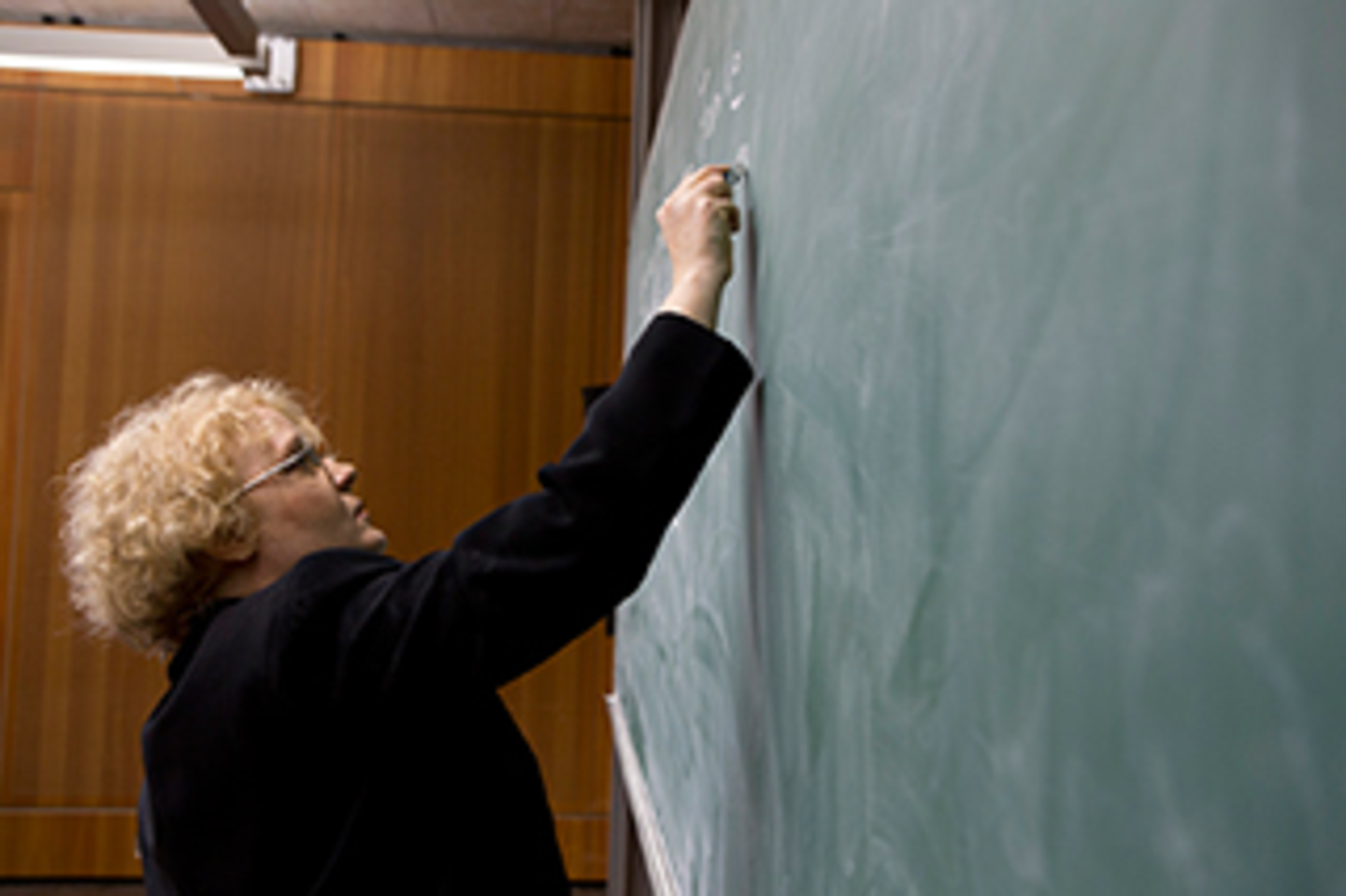A woman is wiriting on a chalk board.