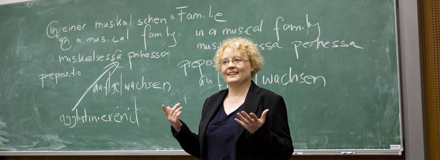 A woman is standing in front of a written on chalk board.