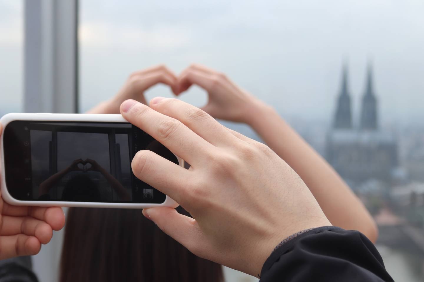 Two hands holding a phone and taking a picture of somebody elses hand forming a heart around the cologne cathedral in the background.