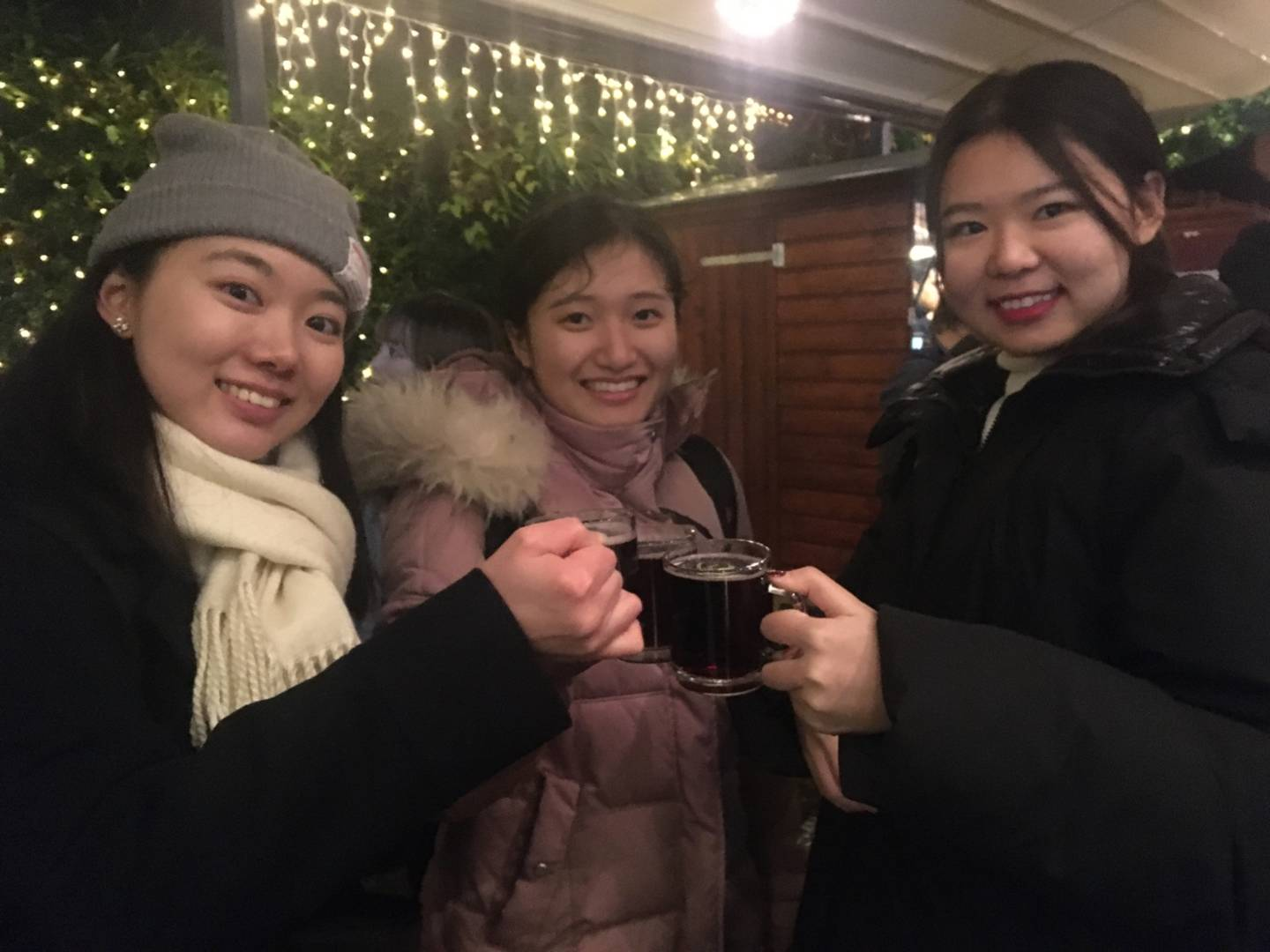 "Three female students clink ""Glühwein""-glasses on the christmas market"