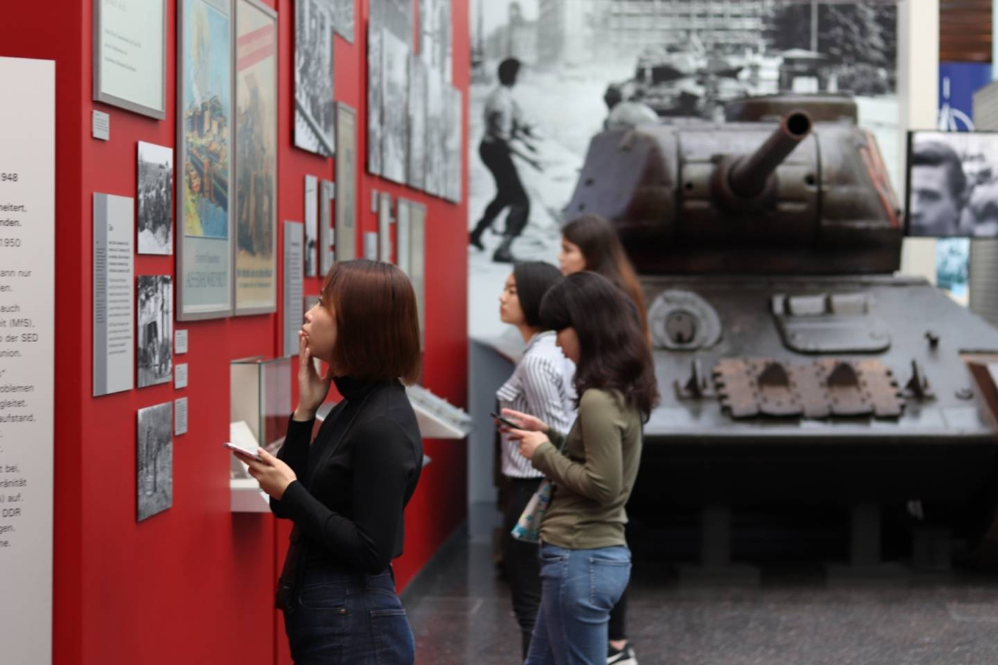 Students looking at the exhibits in the Haus der Geschichte. There is a tank in the background.