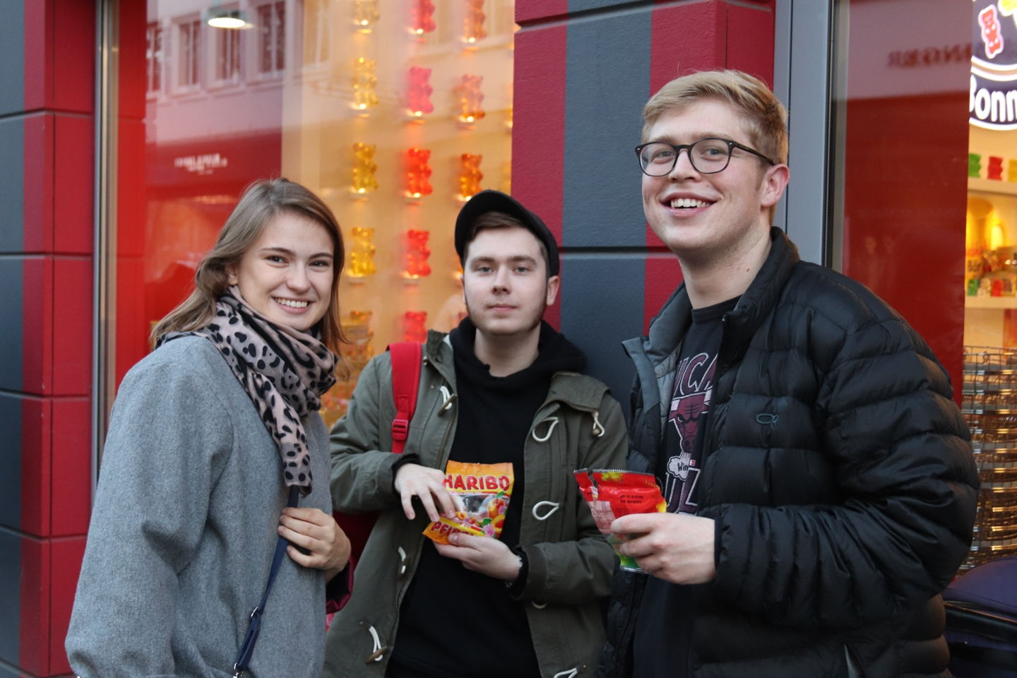 Three students holding bags of Haribo candy in front of the Haribo store.
