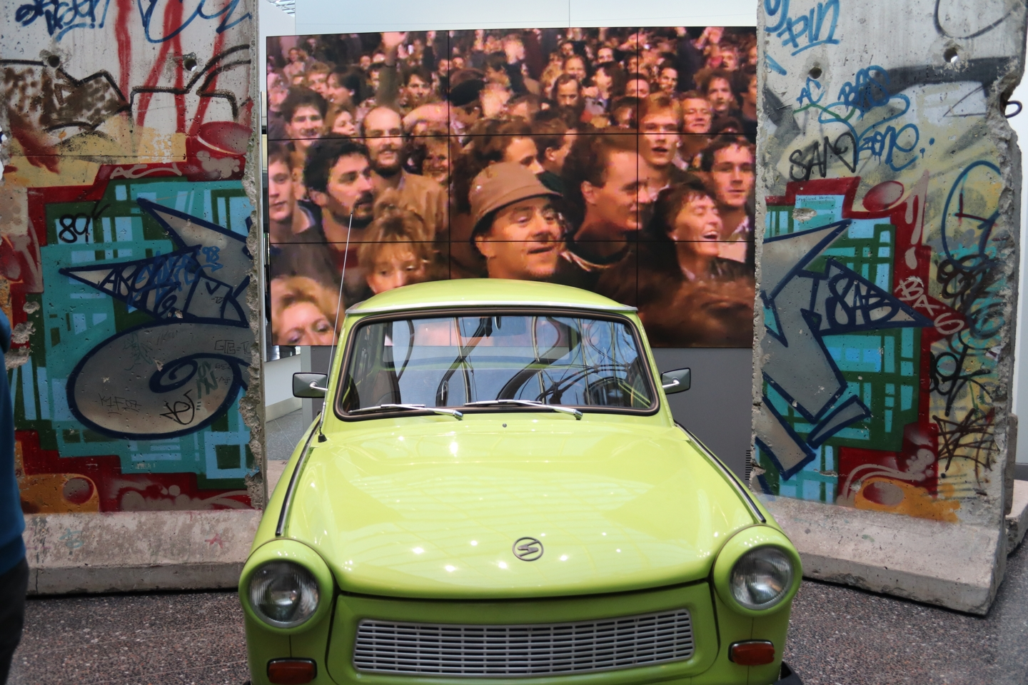 Lime-green Trabant in front of parts of the Berlin Wall.