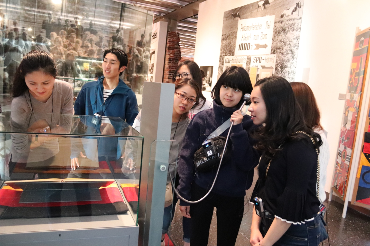 Students looking at exhibits. One student is holding a speaker to her ear and is listening to the explanation.