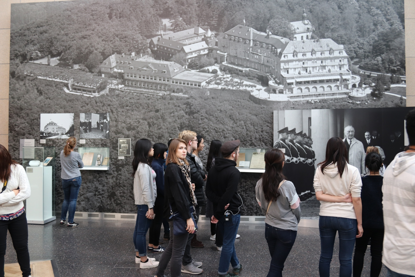 Students standing in front and looking at a huge black and white picture of a building.