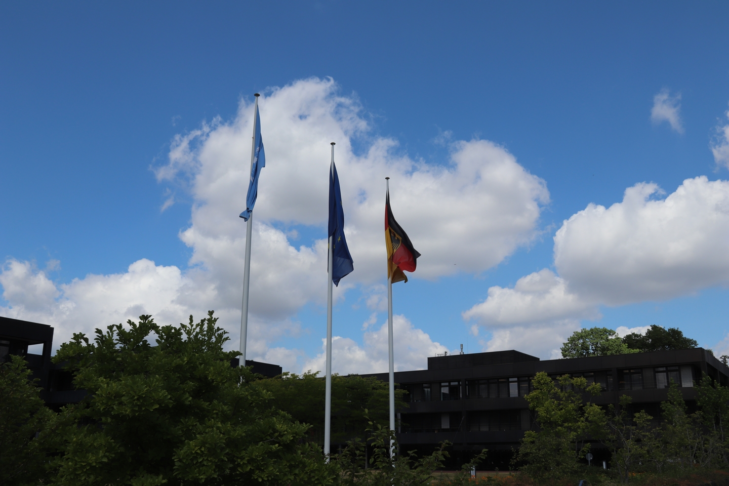 Three flagpoles. One with the german flag, one with the european flag and the last one is the flag of the united nations.