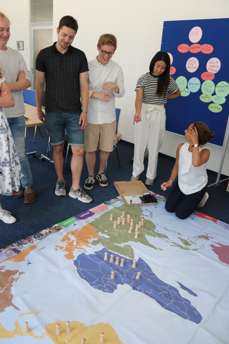 Students playing a game on a big worldmap on the floor.