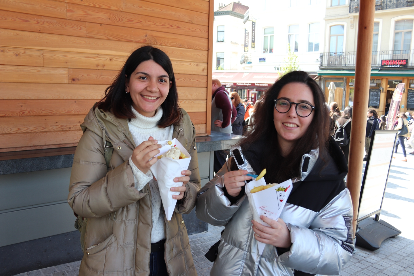 Two female Students with belgian fries in Brussels.