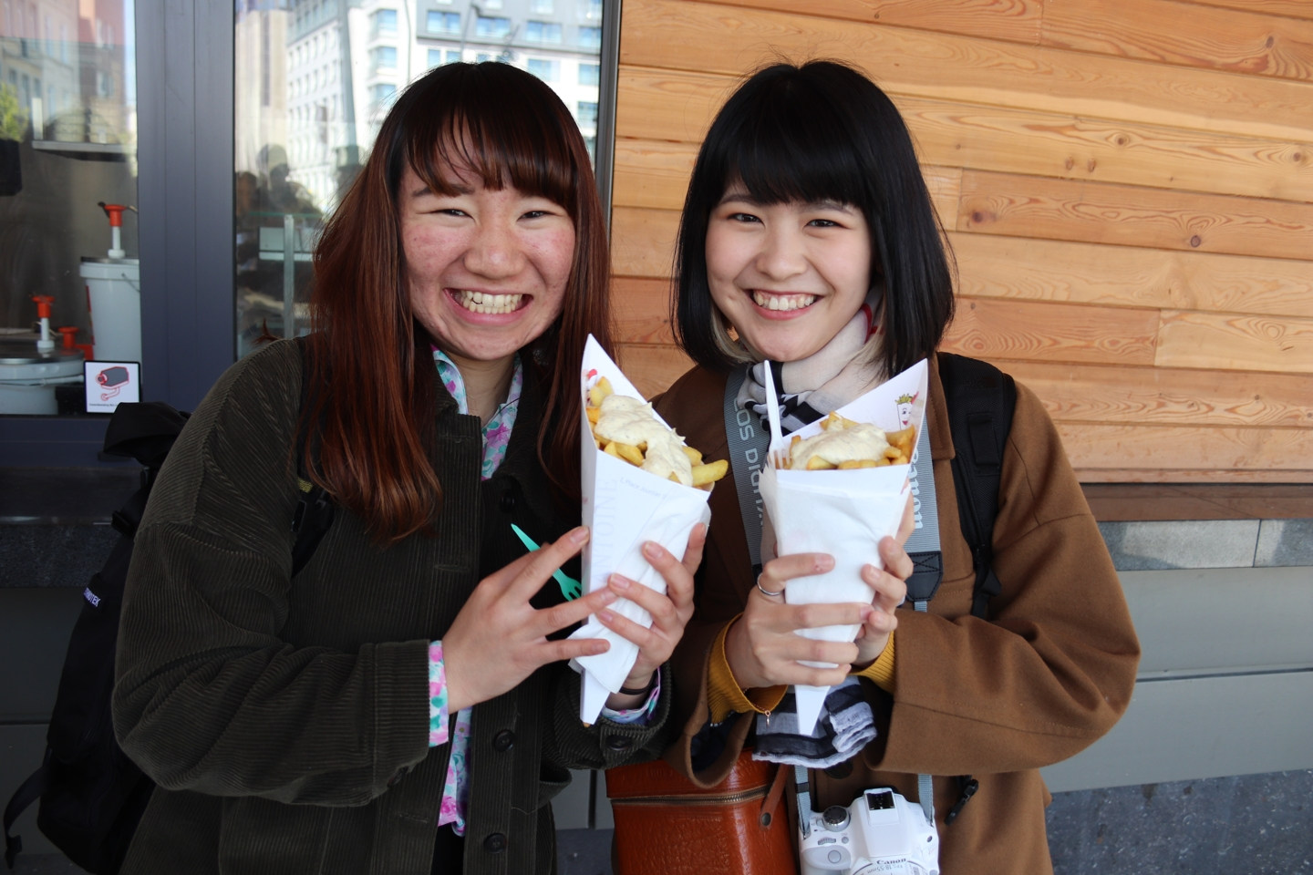 Two students smiling and holding belgian fries