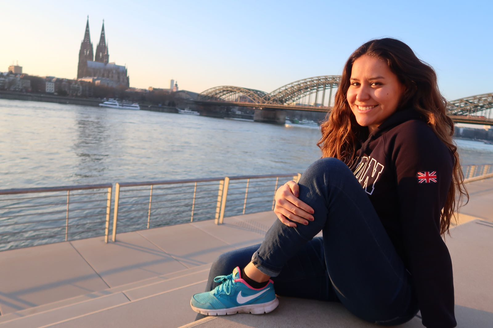 Jaquelin Alonso at the river rhine with the cologne cathedral and hohenzollern bridge in the background.