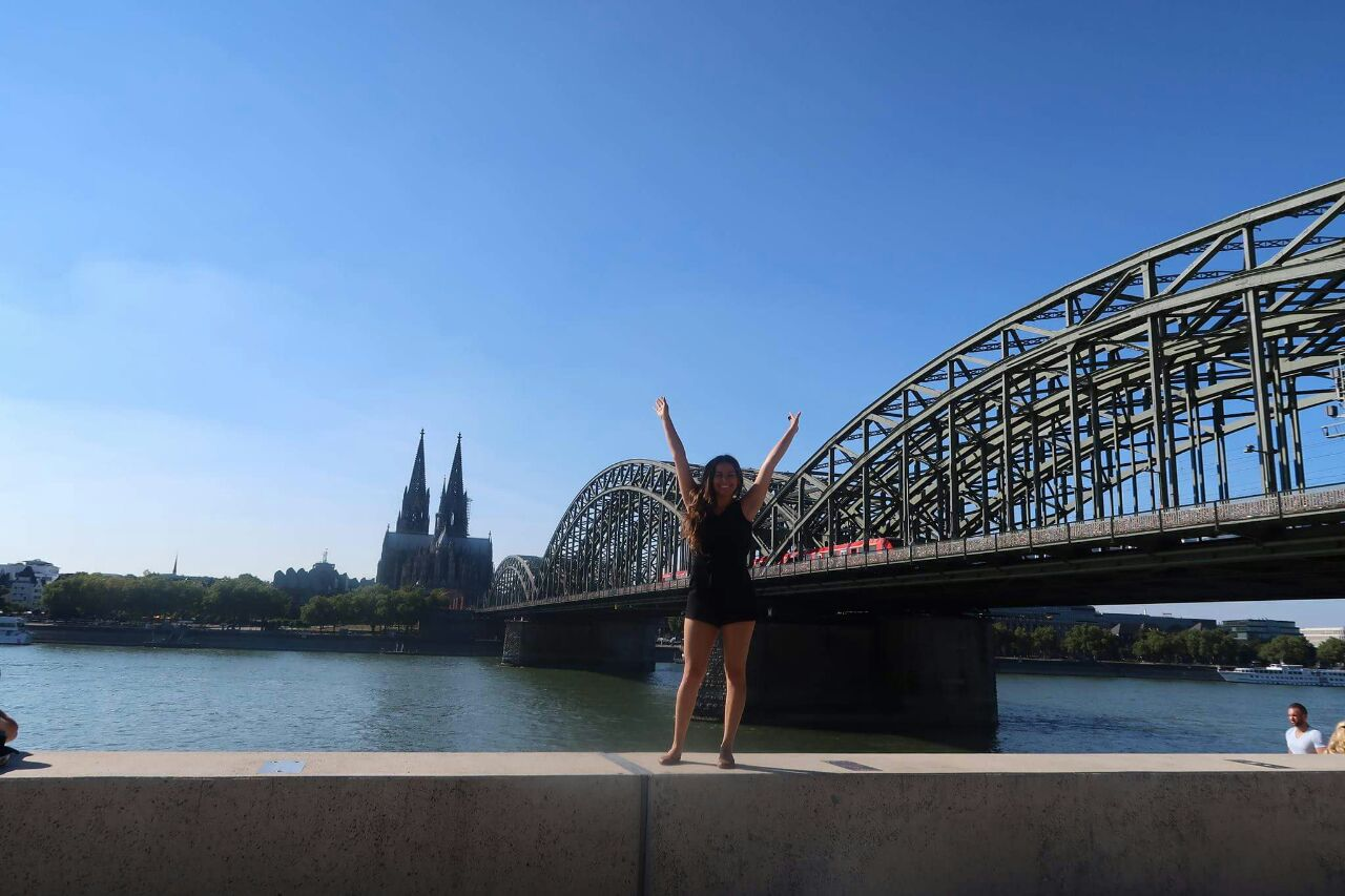 Jaquelin Alonso standing on a wall in front of the river rhine, cologne cathedral and the hohenzollern bridge.