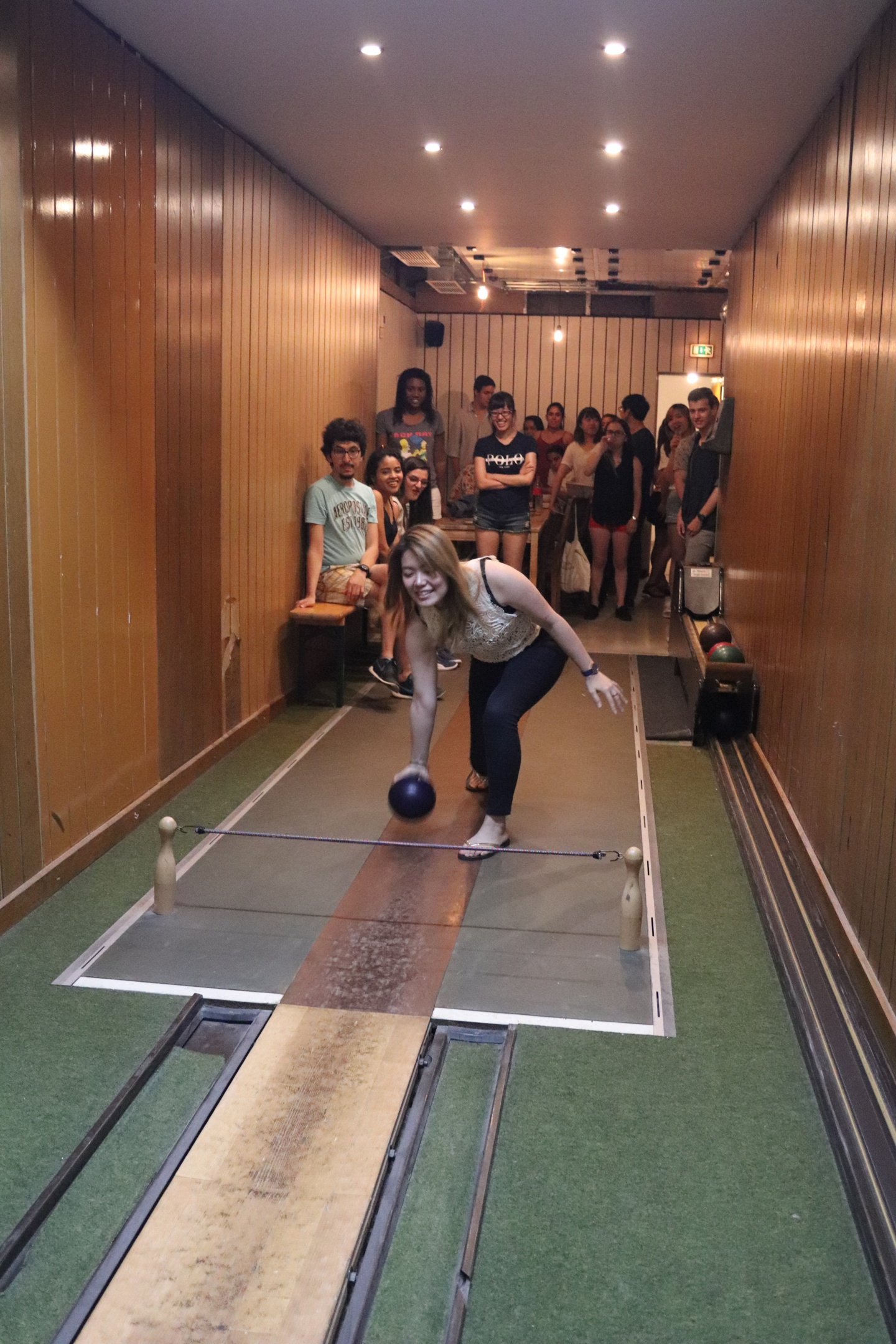 Front view of a student who is about to bowl, with many other students sitting and standing in the background.