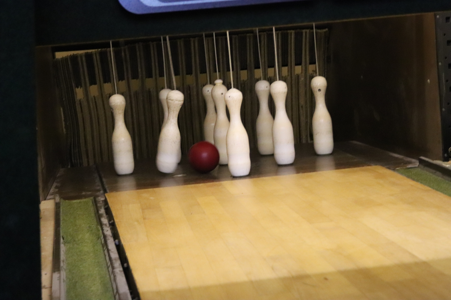 Bowling ball about to hit the bowling pins.