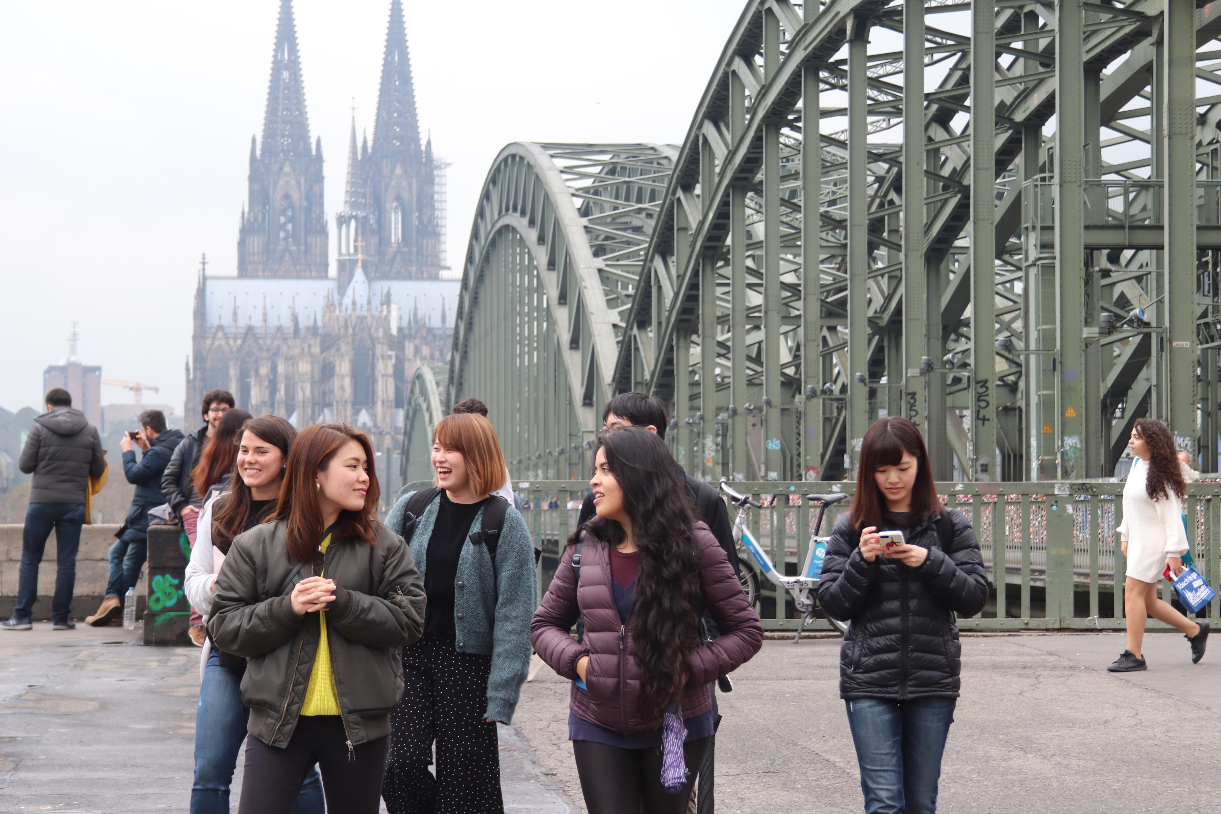Few students in front of the Hohenzollern bridge with the cologne cathedral in the background.