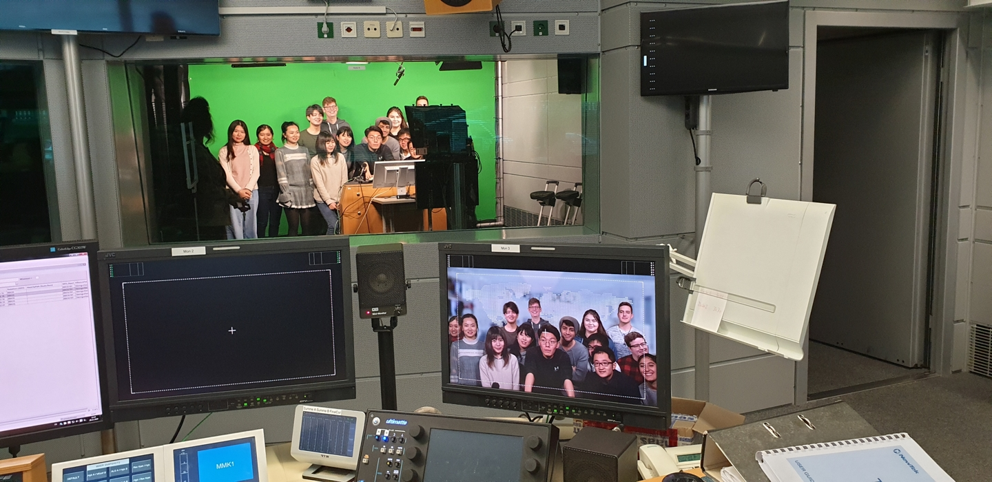 Students in front of a green screen in a recording studio