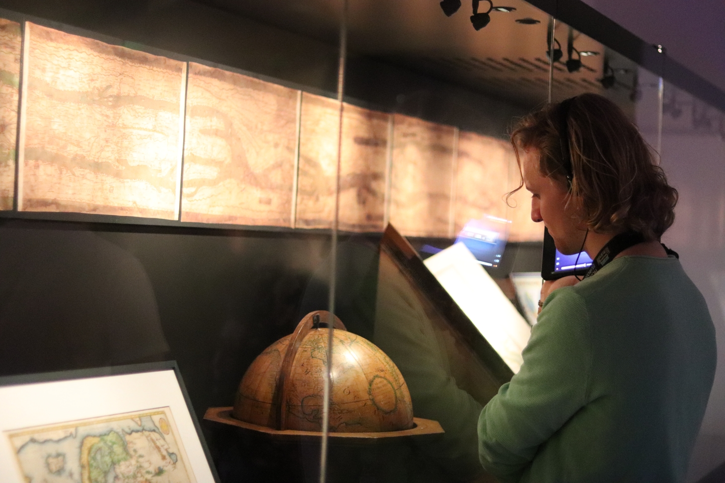 Student looking at the exhibits, an old map and globe, at the museum
