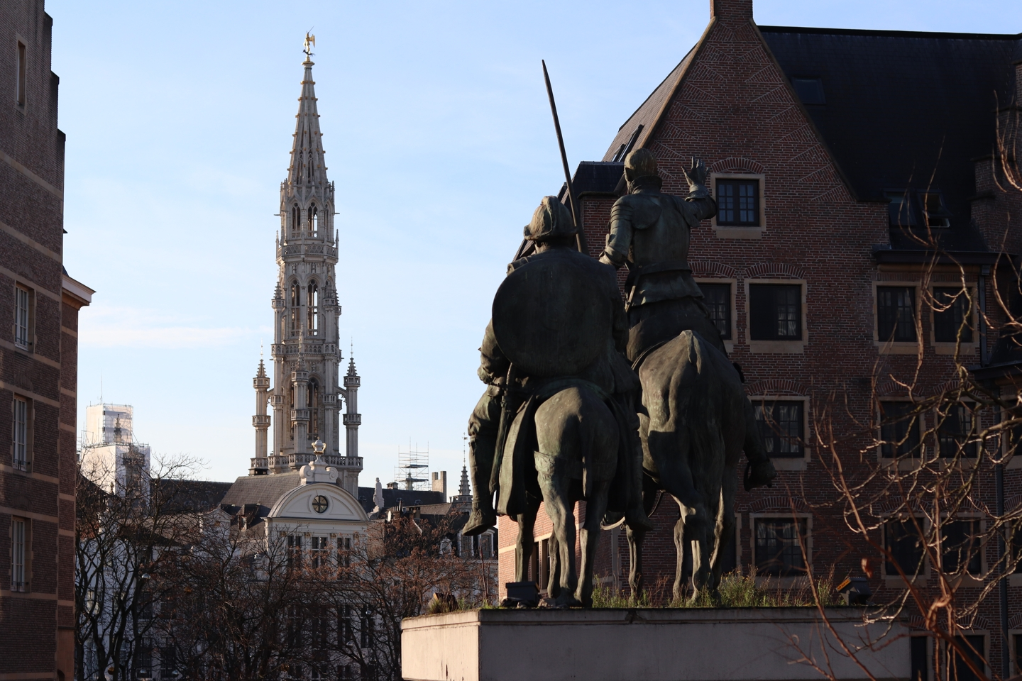 View on the tower of the grote markt and a statue of two people on horses.