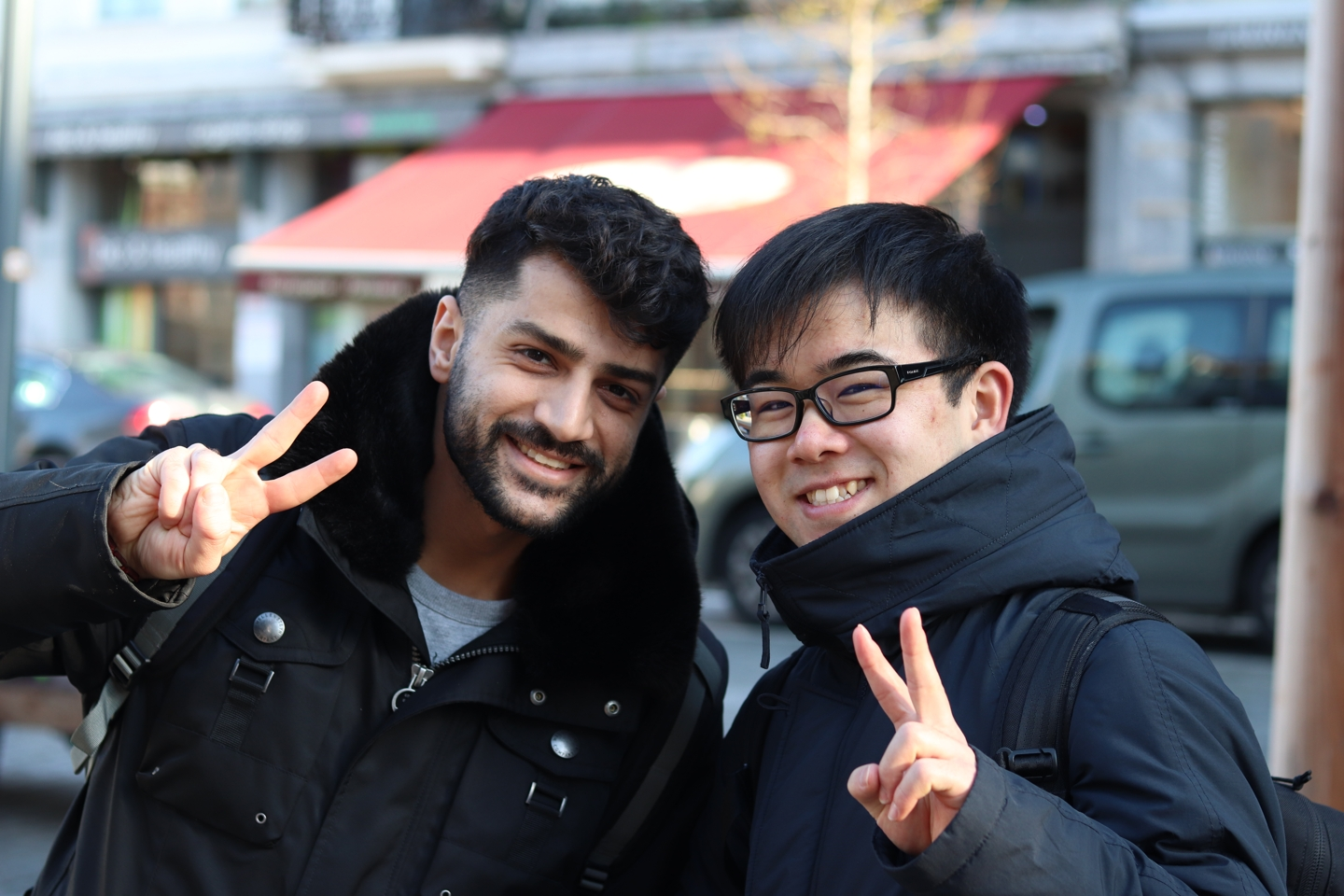 Two students smiling and showing the peace sign at the trip to brussels