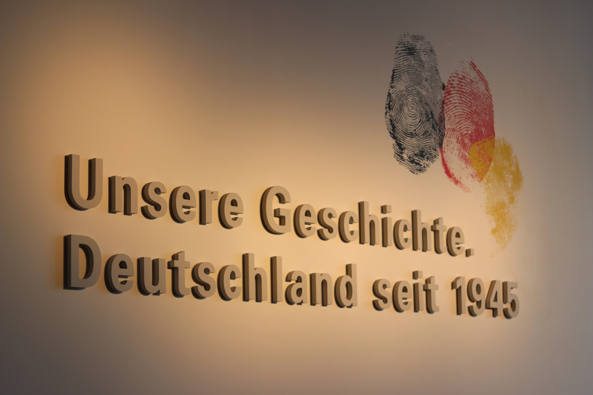 "Letters on the wall froming the sentences. ""Unsere Geschichte. Deutschland seit 1945"" with a black, a red and a golden fingerprint over the lettering."