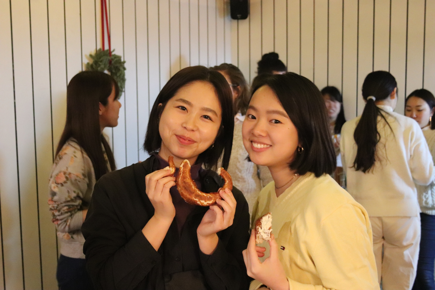 Two girls smiling and holding pretzels in their hands
