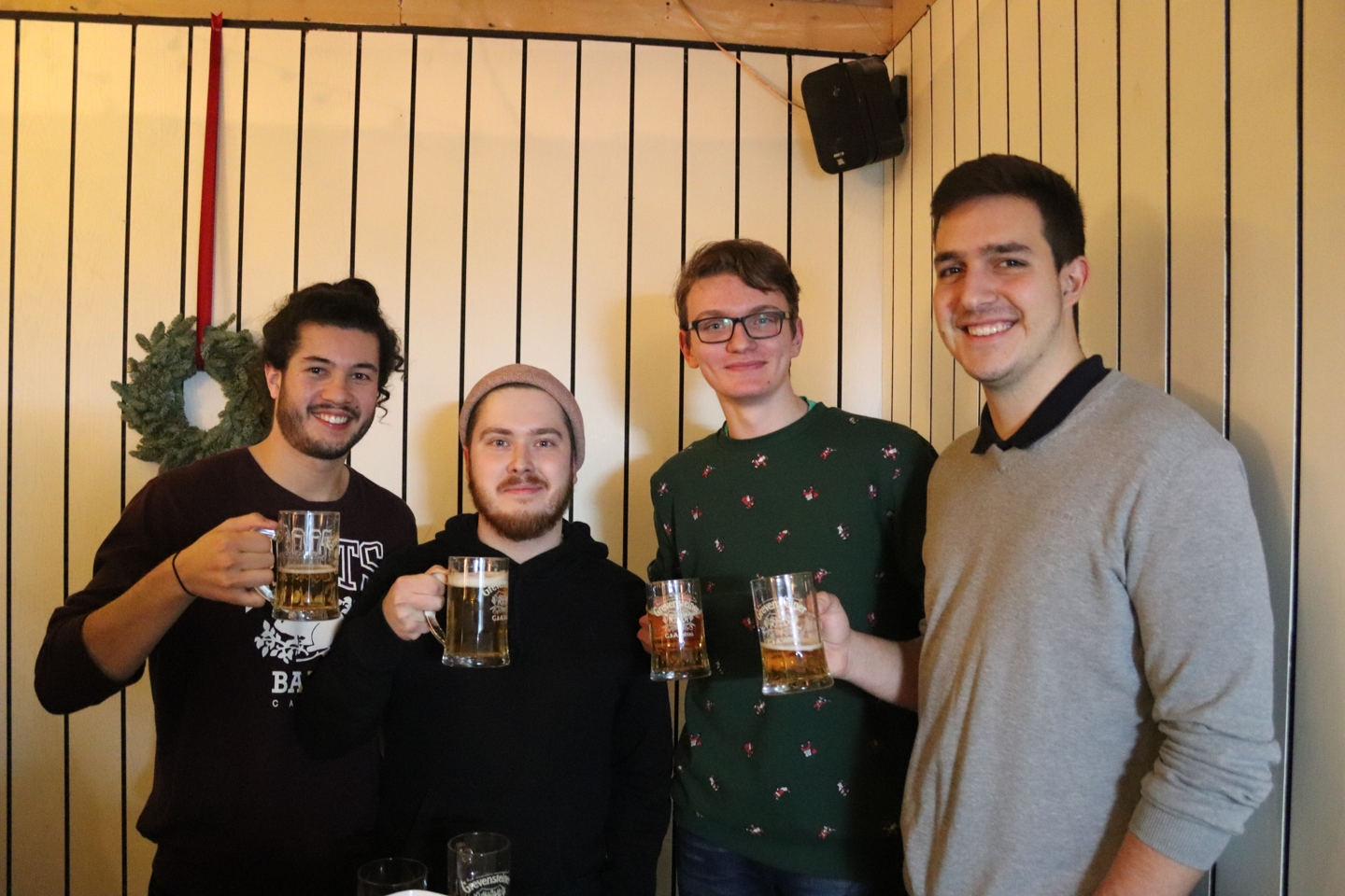 Four smiling male students with beer glasses in their hands.