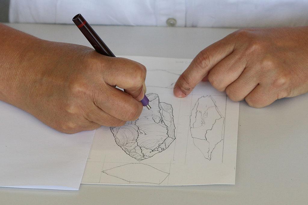 Hand zeichnet einen Faustkeil